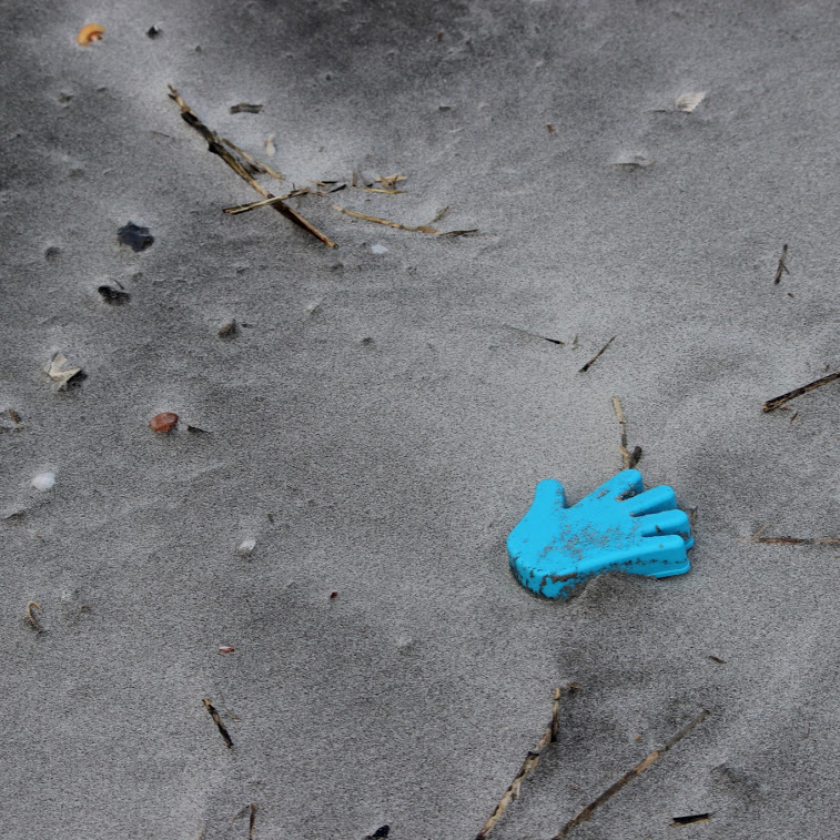 A peice of blue foam shaped like a human hand is shown lying on a beach