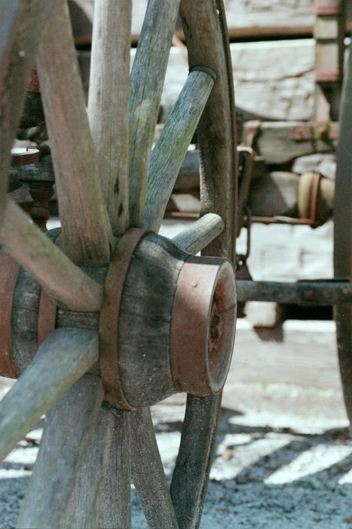 Photo shows the spokes and axle of an old wooden wagon wheel
