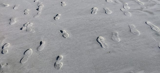 Footprints indented deeply in soft sand on the shore
