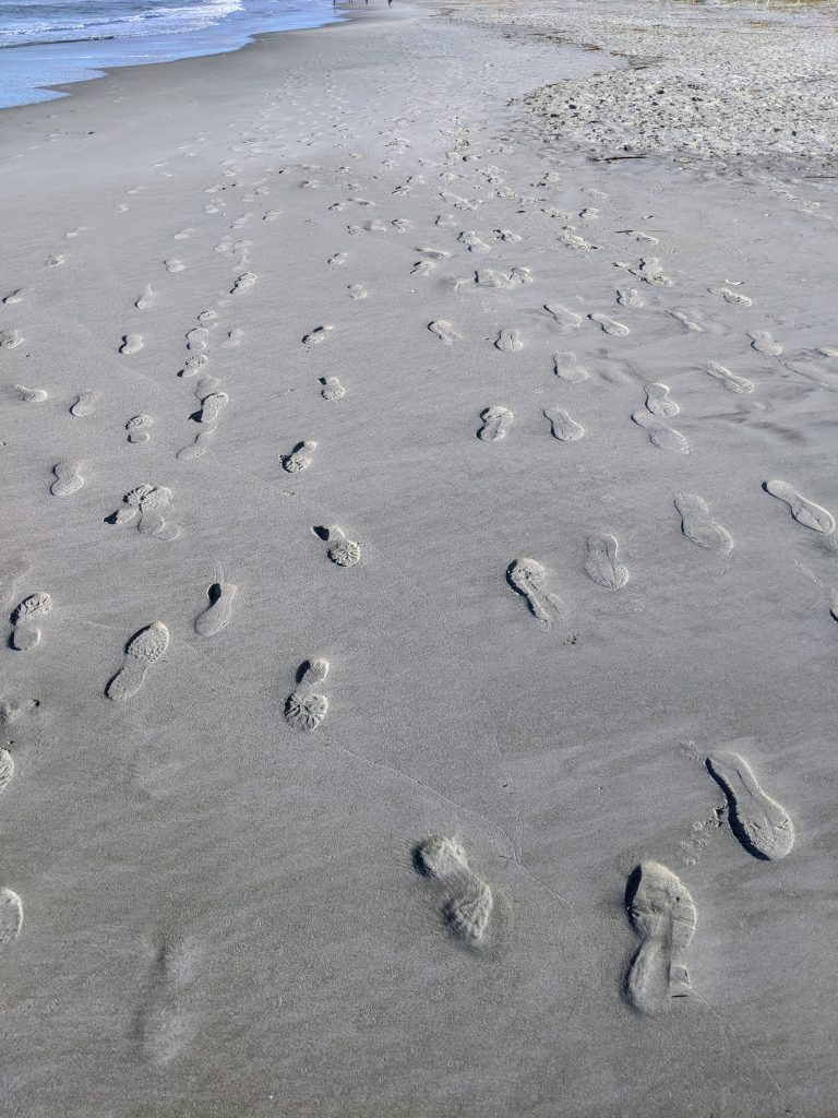 Photo shows the imprints of many shoes in the sand in bright morning light. There are strong shadows cast by the left edges of most of the footprints.